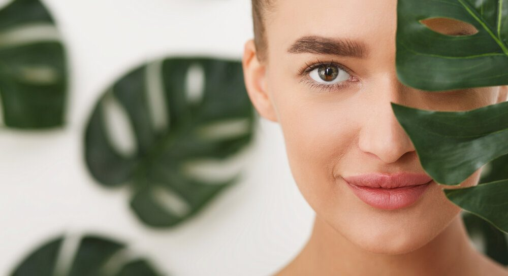 Woman with natural make up and green leaf